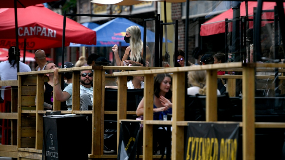 A server wears a mask as she works among the plexiglass dividers at a bar's outdoor patio in the Byward Market in Ottawa, on Sunday, July 12, 2020, in the midst of the COVID-19 pandemic. THE CANADIAN PRESS/Justin Tang