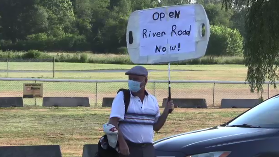 "Hans Reimer holds an ""Open River Road Now"" sign"