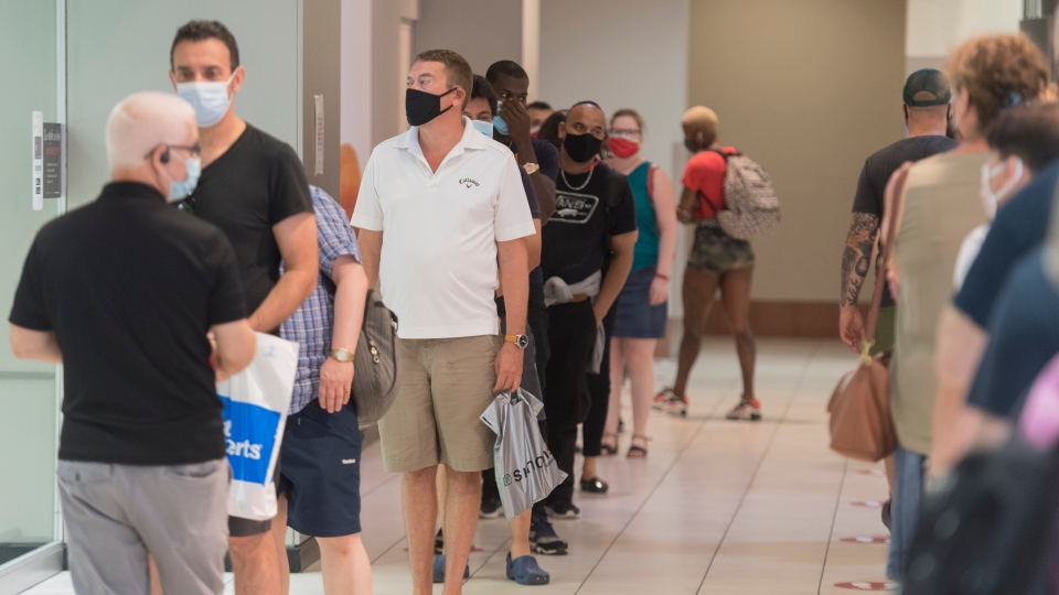 People wear face masks as they wait to enter a department store in Montreal, Saturday, July 18, 2020, as the COVID-19 pandemic continues in Canada and around the world. The wearing of masks or protective face coverings is mandatory in Quebec as of today. THE CANADIAN PRESS/Graham Hughes