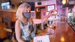 A customer pours some wine at a bar, Tuesday, July 14, 2020 in Montreal. The city has recommended that anyone who has been in a bar since July 1, 2020 to get tested for COVID-19. THE CANADIAN PRESS/Ryan Remiorz