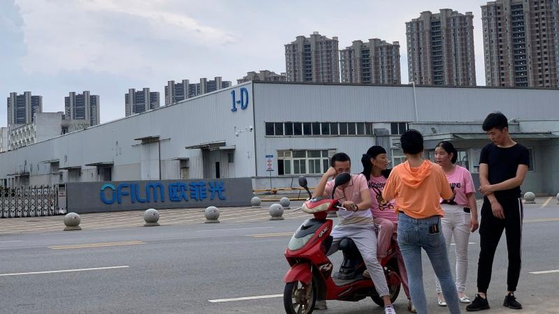 In this June 5, 2019, file photo, neighborhood residents chat near the entrance to an OFILM factory in Nanchang in eastern China's Jiangxi province. (AP Photo/Ng Han Guan, File)