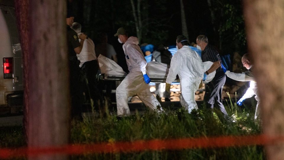 A body believed to be Martin Carpentier is carried by police investigators, Monday, July 20, 2020 in Saint-Apollinaire Que. Romy and Norah Carpentier were found dead in Saint-Apollinaire Que. A man hunt was launched to find the missing father of the two deceased girls. THE CANADIAN PRESS/Jacques Boissinot