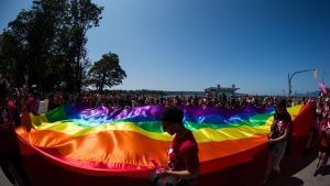 A large rainbow flag is carried by people marching in the Vancouver Pride Parade, in Vancouver, Sunday, Aug. 4, 2019. (Darryl Dyck / THE CANADIAN PRESS)