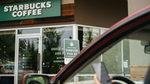 A customer drives up to a Starbucks for curbside pickup.