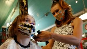 Robin Sotomayor, 5, wears a supergirl face mask as she gets her hair done by Haylee Cummins at Rockabetty's Hair Parlor, in Yuba City, Calif., Monday, May 4, 2020. (AP Photo/Rich Pedroncelli, File)
