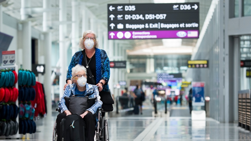 "Elderly people wearing mandatory masks walk to their gate at Toronto's Pearson International Airport for a ""Healthy Airport"" during the COVID-19 pandemic in Toronto on Tuesday, June 23, 2020. THE CANADIAN PRESS/Nathan Denette"
