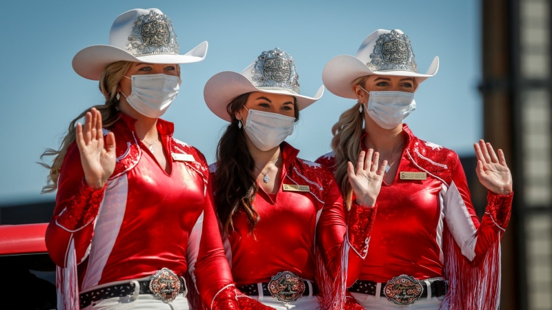 Calgay Stampede princesses Janelle MacKenzie, left to right, Kelcey Moore, and Madeline Kerkovius, wave to visitors during a drive-thru pancake breakfast as people try to enjoy the Calgary Stampede even though it has been cancelled in Calgary, Saturday, July 4, 2020. THE CANADIAN PRESS/Jeff McIntosh