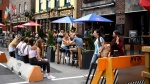 People sit at an outdoor patio at a bar in the ByWard Market in Ottawa, as others wait for a table, on Sunday, July 12, 2020, in the midst of the COVID-19 pandemic. (Justin Tang/THE CANADIAN PRESS)