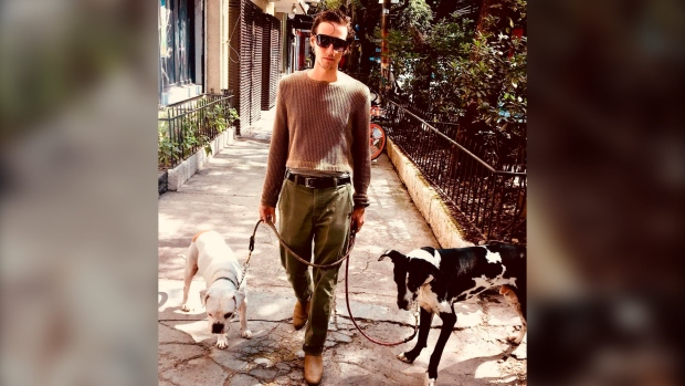 In this photo courtesy of Sophie Fustec shows her brother Pablo Fustec walking his dogs Sasha, right, and Felipe in Mexico City in Nov. of 2019. (Sophie Fustec via AP)