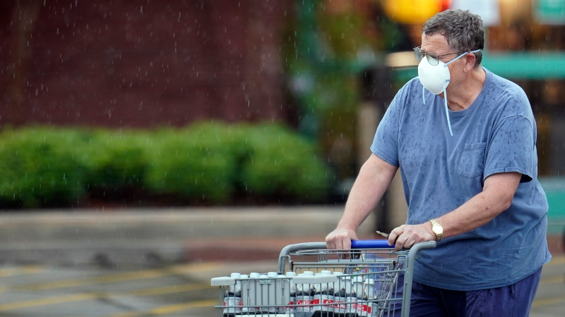 A shopper wears a mask as he pushes a grocery cart in the rain Thursday, June 25, 2020, in Houston. (AP Photo/David J. Phillip)