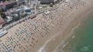 Beachgoers practice social distancing in Spain