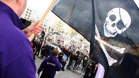 One of the hundreds of supporters of file-sharing hub The Pirate Bay that demonstrated in Stockholm, Sweden on Saturday April 18 2009, waves a Jolly Roger, pirate flag while Sweden's Pirate Party chairman and founder Rickard Falkvinge talks in the background. (Scanpix Sweden / Fredrik Persson)