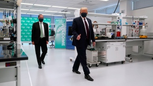 U.S. Health and Human Services Secretary Alex Azar, left, and President Donald Trump participate in a tour of Bioprocess Innovation Center at Fujifilm Diosynth Biotechnologies, Monday, July 27, 2020, in Morrisville, N.C. (AP Photo/Evan Vucci)