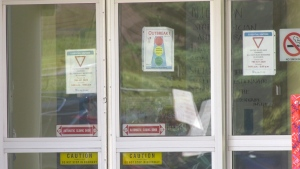 "An ""outbreak"" sign is posted to the front door of the Good Samaritan Southgate Care Centre. (File photo.)"