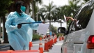 Healthcare worker Dante Hills, left, passes paperwork to a woman in a vehicle at a COVID-19 testing site outside of Marlins Park, Monday, July 27, 2020, in Miami.. (AP / Lynne Sladky)
