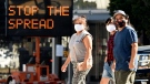 Pedestrians wear masks as they walk in front of a sign reminding the public to take steps to stop the spread of coronavirus, July 23, 2020, in Glendale, Calif. (AP Photo/Chris Pizzello)