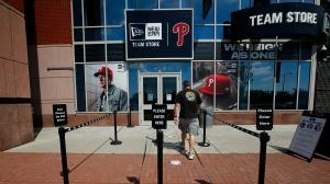 A person walks toward the Philadelphia Phillies team store at Citizens Bank Park on Monday, July 27, 2020, in Philadelphia. (Yong Kim/The Philadelphia Inquirer via AP)