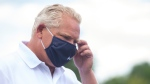 Ontario Premier Doug Ford removes his mask as he steps to the microphone during an announcement in Ajax, Ont., on Tuesday, July 28, 2020. THE CANADIAN PRESS/Chris Young
