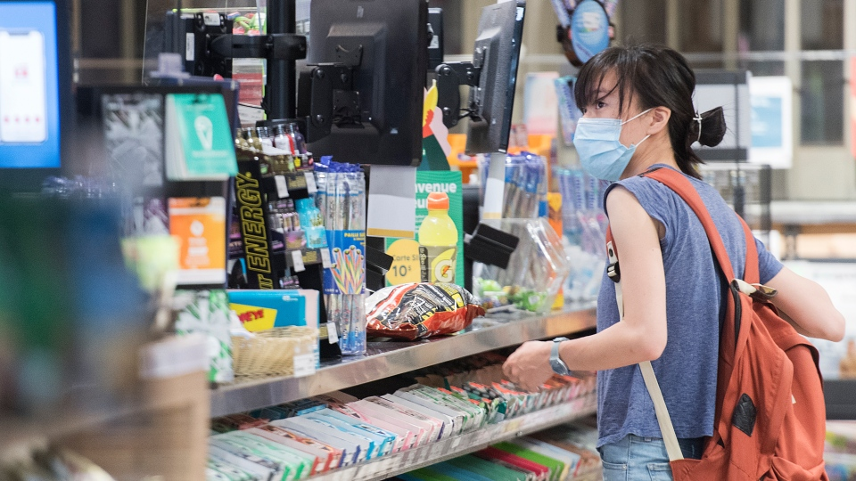 A woman wears a face mask at a convenience store in Montreal, Sunday, July 19, 2020, as the COVID-19 pandemic continues in Canada and around the world. The wearing of masks or protective face coverings is mandatory in Quebec as of July 18. THE CANADIAN PRESS/Graham Hughes