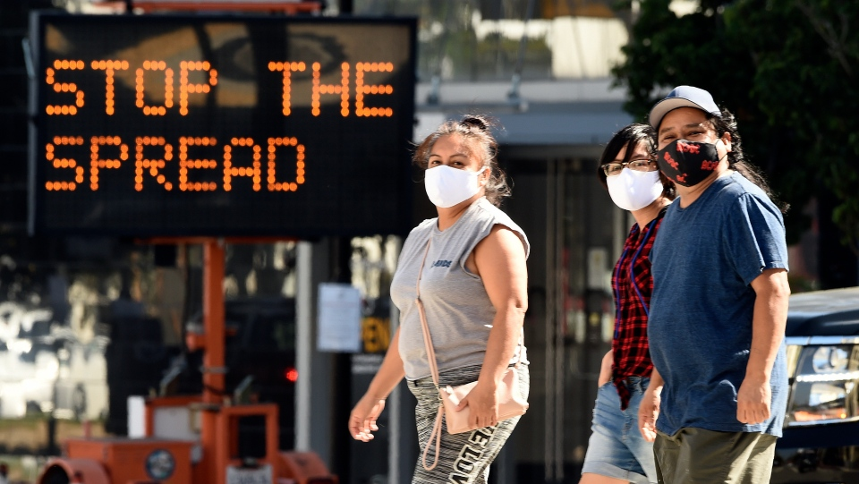 Pedestrians wear masks as they walk in front of a sign reminding the public to take steps to stop the spread of coronavirus, Thursday, July 23, 2020, in Glendale, Calif. (AP Photo/Chris Pizzello, File)