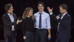 Co-founders Craig (left) and Marc Kielburger introduce Prime Minister Justin Trudeau and his wife Sophie Gregoire-Trudeau as they appear at the WE Day celebrations in Ottawa on November 10, 2015. (THE CANADIAN PRESS/Adrian Wyld)