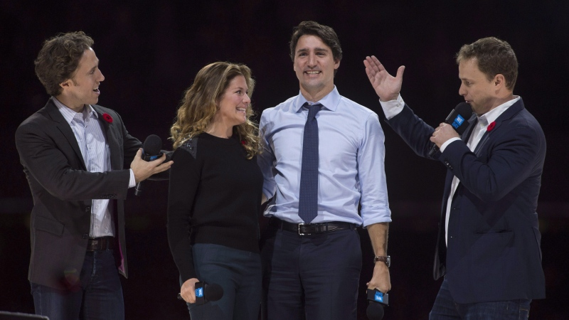 Co-founders Craig (left) and Marc Kielburger introduce Prime Minister Justin Trudeau and his wife Sophie Gregoire-Trudeau as they appear at the WE Day celebrations in Ottawa on November 10, 2015. THE CANADIAN PRESS/Adrian Wyld