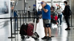 """A man wearing a mask and full face shield talk on the phone at Toronto's Pearson International Airport for a """"Healthy Airport"""" during the COVID-19 pandemic in Toronto on Tuesday, June 23, 2020. THE CANADIAN PRESS/Nathan Denette"""