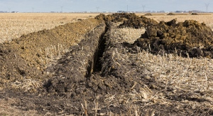 A trench is excavated in a farm field for water drainage pipe installation in this file photo.