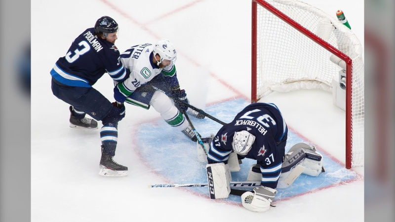 Winnipeg Jets' Tucker Poolman (3) and goaltender Connor Hellebuyck (37) defend the net against Vancouver Canucks' Brandon Sutter (20) during second period NHL exhibition game action in Edmonton, on Wednesday, July 29, 2020. THE CANADIAN PRESS/Codie McLachlan