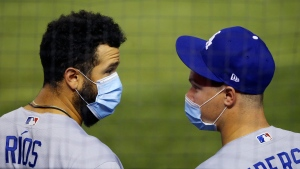 With face coverings on, Los Angeles Dodgers' Edwin Rios, left, and Joc Pederson talk in the dugout during the sixth inning of the team's baseball game against the Arizona Diamondbacks, who were playing their home-opener, Thursday, July 30, 2020, in Phoenix. (AP Photo/Ross D. Franklin)