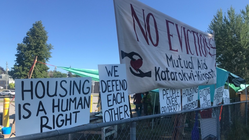 Signs at a temporary campsite at Belle Park in Kingston, calling on the City to find proper housing solutions for the campers. (Kimberley Johnson / CTV News Ottawa)