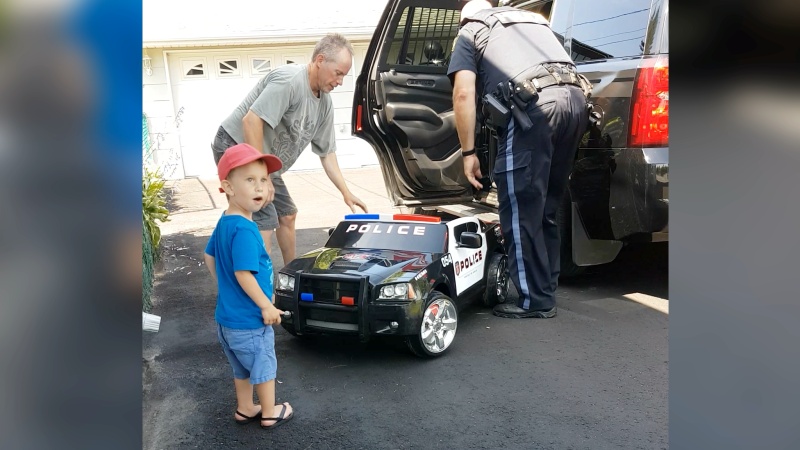 Young Chase, reacting to a gift of a battery-powered police cruiser from Const. Craig Kelso. (Photo courtesy of Patty Baird)