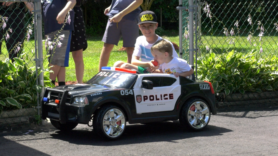 Chase and brother Breck with their new battery-powered police car. (Nate Vandermeer / CTV News Ottawa)