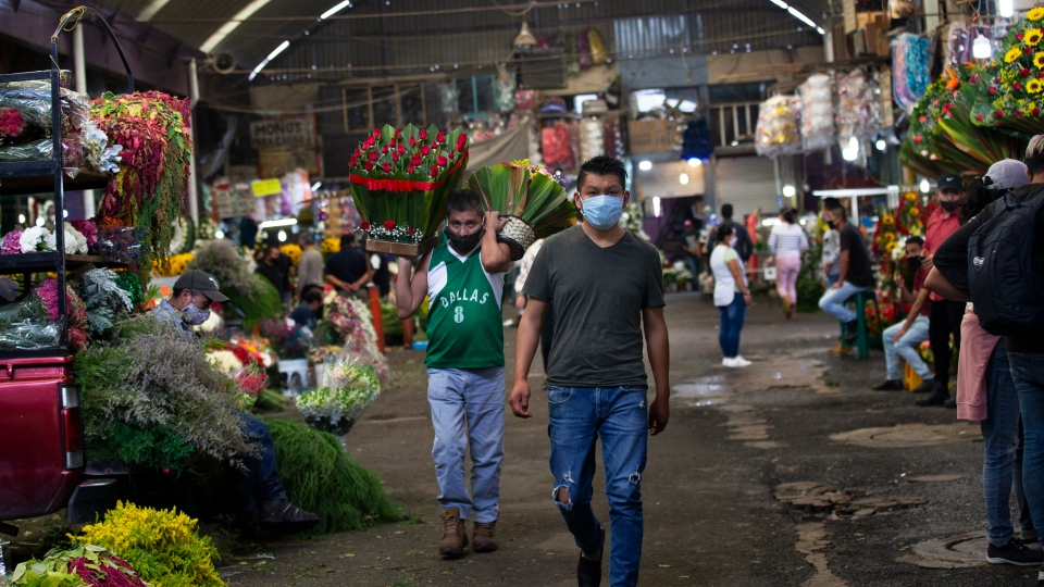 People wear masks to curb the spread of the new coronavirus inside Mexico City's Jamaica market, Thursday, July 30, 2020. (AP Photo/Marco Ugarte)
