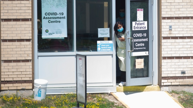 A staff member peers out of a COVID testing centre at a Hospital in Ajax, Ont., on Tuesday July 28, 2020. THE CANADIAN PRESS/Chris Young