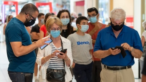 Shoppers wear masks as they line up at a mall on the third day of Quebec's mandatory mask order for all indoor public spaces 20, 2020 in Laval, Que. THE CANADIAN PRESS/Ryan Remiorz