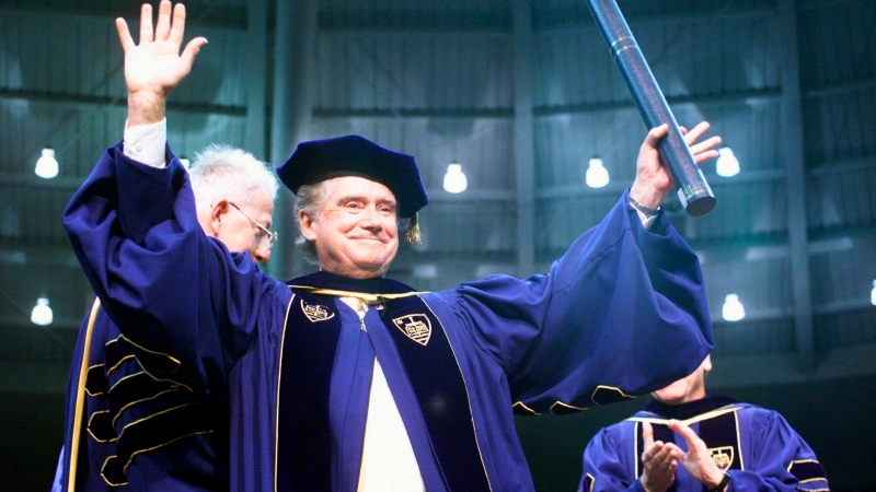 In this May 16, 1999, file photo, Regis Philbin, a Notre Dame graduate, waves to the crowd after receiving an honorary degree during Notre Dame's 154th commencement exercises in South Bend, Ind. Philbin, who died last week at 88, has been buried at the university's Cedar Grove Cemetery, following a private funeral service Wednesday, July 29, 2020. (AP Photo/Joe Raymond)