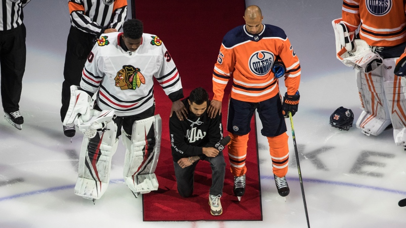 Minnesota Wild's Matt Dumba takes a knee during the national anthem flanked by Edmonton Oilers' Darnell Nurse, right, and Chicago Blackhawks' Malcolm Subban before an NHL playoff game in Edmonton, Saturday, Aug. 1, 2020. THE CANADIAN PRESS/Jason Franson