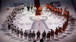 Minnesota Wild's Matt Dumba takes a knee during the national anthem as he is surrounded by the Edmonton Oilers and Chicago Blackhawks before an NHL playoff game in Edmonton, Saturday, Aug. 1, 2020. THE CANADIAN PRESS/Jason Franson