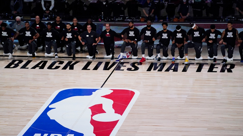 Players kneel before an NBA basketball game between the Los Angeles Lakers and the Toronto Raptors, Saturday, Aug. 1, 2020, in Lake Buena Vista, Fla. (AP Photo/Ashley Landis, Pool)