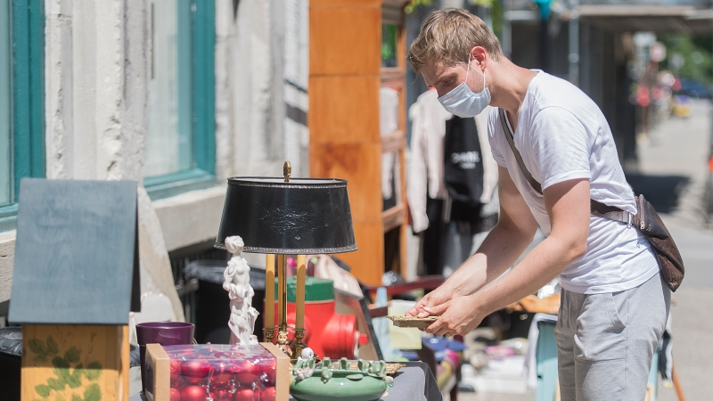 Jean-Christophe Martel wears a face mask as he sets up some of his belongings as he hosts a garage sale in Montreal, Saturday, August 1, 2020. THE CANADIAN PRESS/Graham Hughes