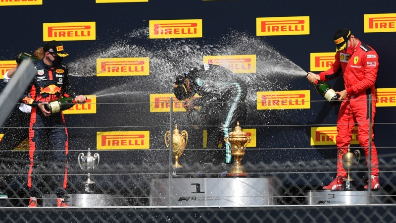 Mercedes driver Lewis Hamilton of Britain, center, celebrates his victory on the podium with second placed Red Bull driver Max Verstappen of the Netherlands, left and third placed Ferrari driver Charles Leclerc of Monaco the British Formula One Grand Prix at the Silverstone racetrack, Silverstone, England, Sunday, Aug. 2, 2020. (Ben Stansall/Pool via AP)