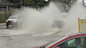 Cars drive through pooled water after heavy rain in Barrie, Ont. on Sunday August 2, 2020 (Don Wright/CTV News)