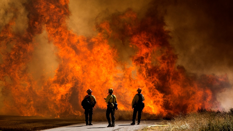 Firefighters watch as flames flare at the Apple Fire in Cherry Valley, Calif., Saturday, Aug. 1, 2020. A wildfire northwest of Palm Springs flared up Saturday afternoon, prompting authorities to issue new evacuation orders as firefighters fought the blaze in triple-degree heat.(AP Photo/Ringo H.W. Chiu)