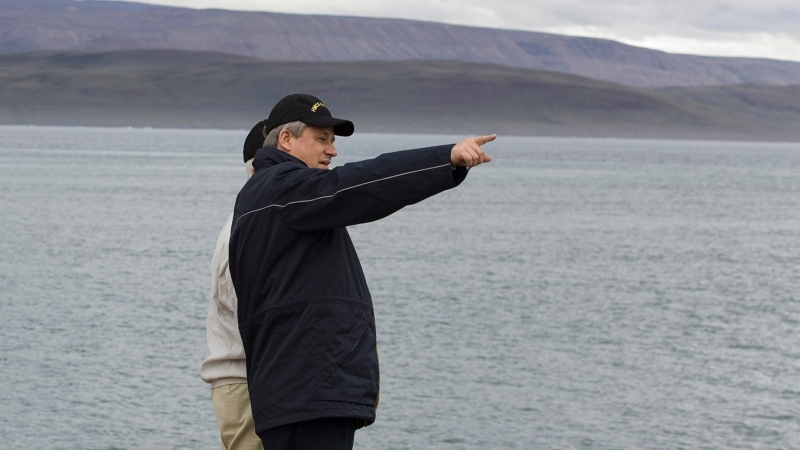 Former prime minister Stephen Harper looks down the shoreline in the Arctic port of Nanisivik, Nunavut on August 10, 2007. (THE CANADIAN PRESS/Fred Chartrand)