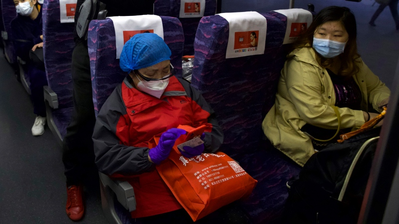 Passengers wearing face masks to protect against the spread of new coronavirus board a high-speed train in Wuhan in central China's Hubei Province, Wednesday, April 8, 2020. (AP Photo/Ng Han Guan)