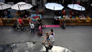 People sit in outdoor booths, built on top of street parking spots outside a restaurant as people walk on a road closed to car traffic in the Byward Market in Ottawa, on Sunday, July 12, 2020. (THE CANADIAN PRESS / Justin Tang)