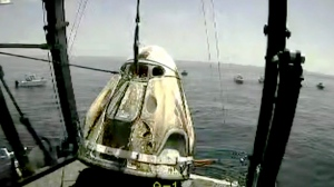 In this frame grab from NASA TV, the SpaceX capsule is lifted onto a ship, Sunday, Aug. 2, 2020 in the Gulf of Mexico. (NASA TV via AP)