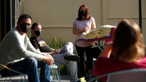 Residents at a Uniting Gen Regen AOD residential facility try on new masks in Melbourne, Thursday, July 30, 2020. Australia's coronavirus hot spot, Victoria state, will make wearing masks compulsory after reporting a record more than 700 new cases on Thursday, mostly among the vulnerable residents of aged care homes. (Daniel Pockett/AAP Image via AP)