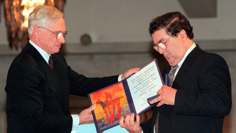 In this Dec. 10, 1998 file photo, John Hume, right, looks at the Nobel Peace Prize diploma which he received from Francis Sejersted, left, chairman of the Norwegian Nobel Peace Prize Committee during the award ceremony in Oslo Town Hall. (AP Photo/Bjoern Sigurdsoen/NTB/POOL)